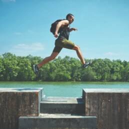 Ragazzo che salta uno scalino vicino a un lago