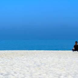Ragazza che fa Yoga in riva al mare